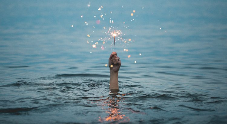Holding hand above water with sparkler