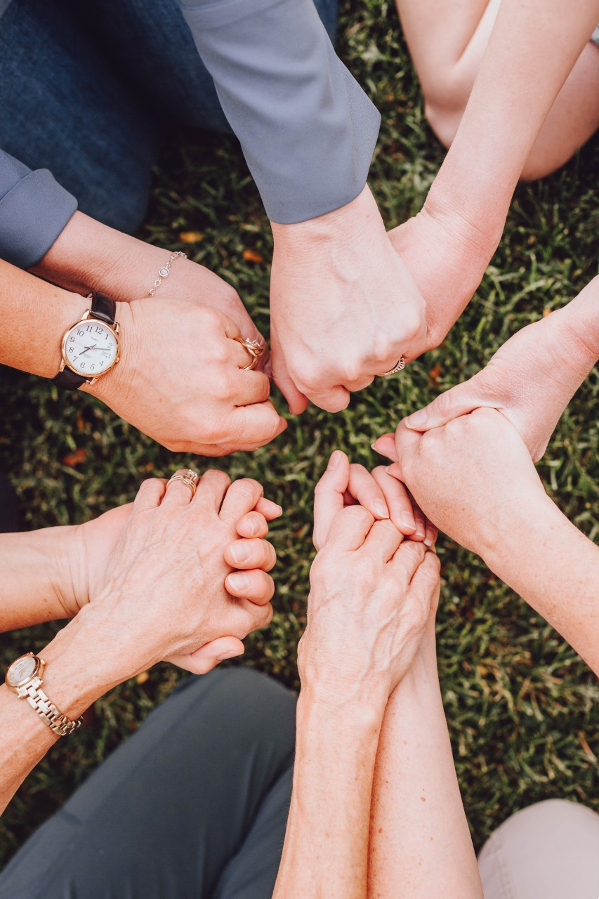 Women holding hands as they support each other